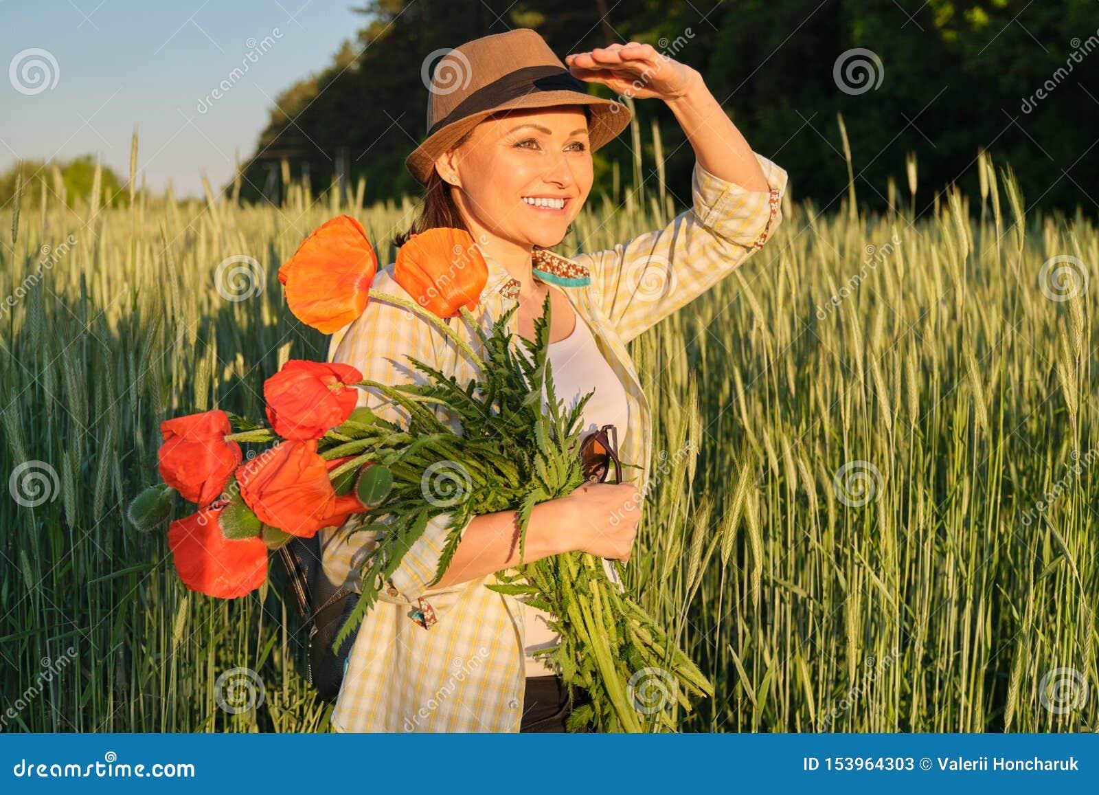 Porträt im Freien der glücklichen reifen Frau mit Blumensträußen von roten Mohnblumenblumen