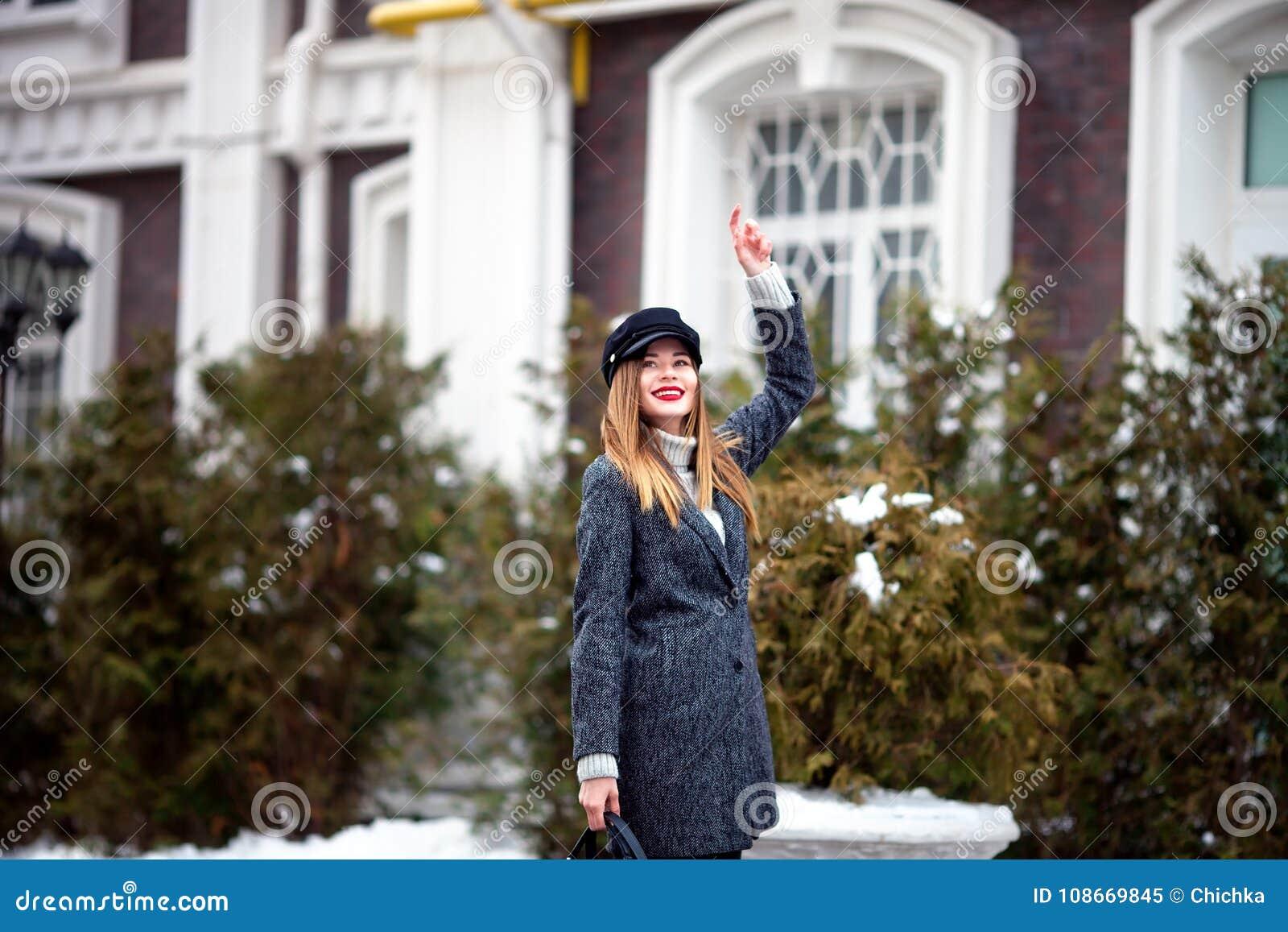 Porträt im Freien der jungen schönen modernen Frau, die modische Kappe trägt Stilvolle Kleidung und Zubehör Vorbildliches Gehen i