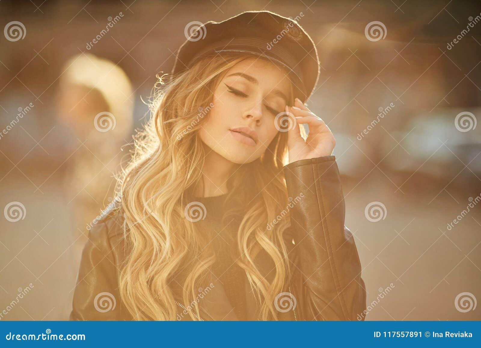 Porträt im Freien der jungen schönen modernen und sinnlichen Frau in der schwarzen Lederjacke und im stilvollen Hut mit Make-up u