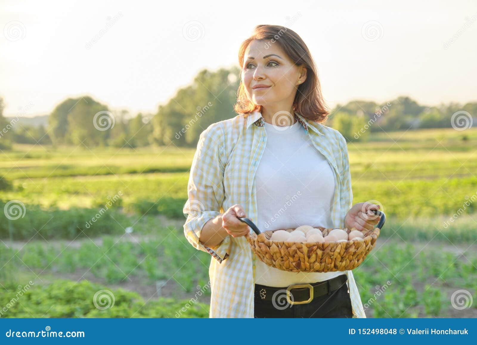 Porträt im Freien der Landwirtfrau mit Korb von frischen Hühnereien, Bauernhof