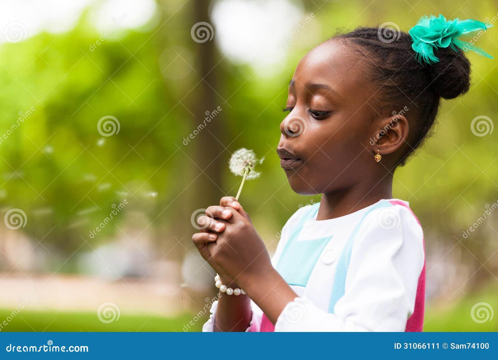 Porträt im Freien eines netten jungen schwarzen Mädchens, das einen Löwenzahn durchbrennt