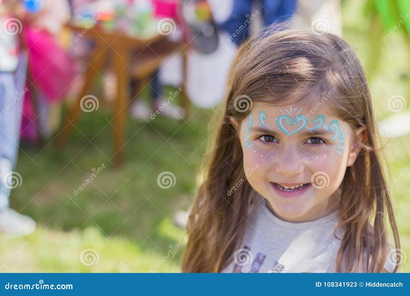 Porträt im Freien eines schönen kleinen Mädchens mit gemaltem Gesicht