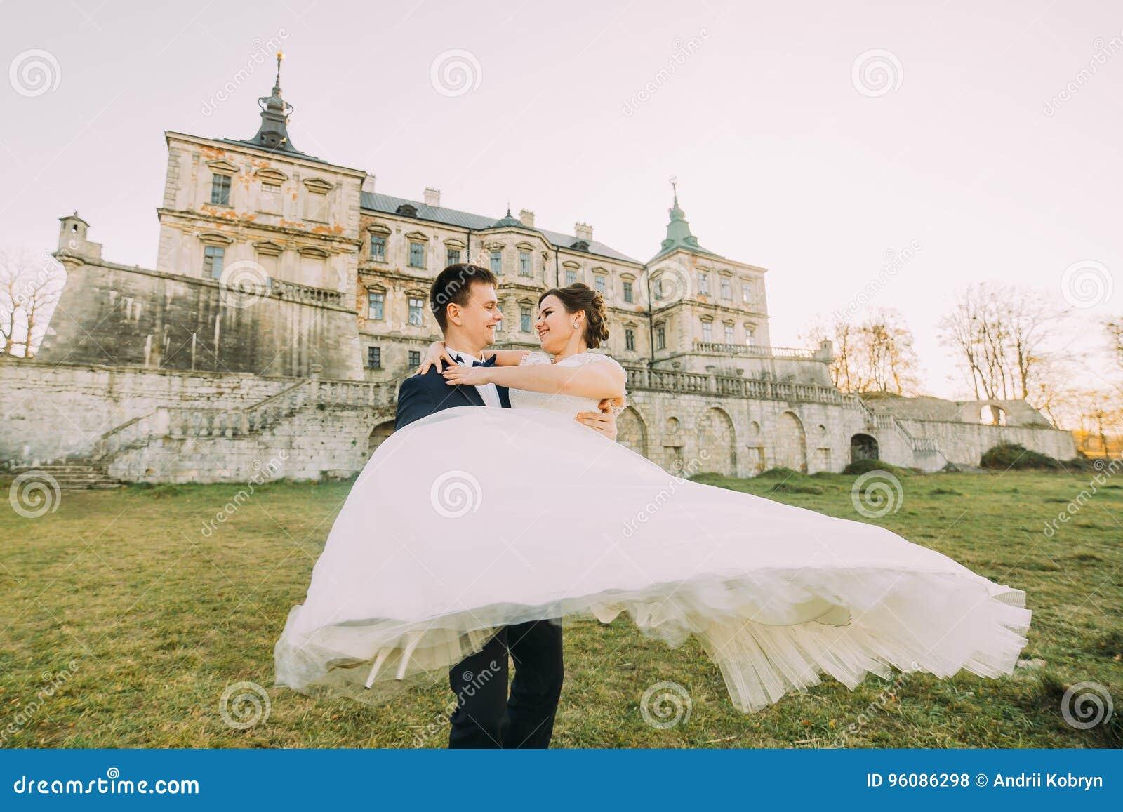 Porträt im Freien vom netten gerade geheiratet am Hintergrund des antiken Palastes Der Bräutigam spinnt die Braut