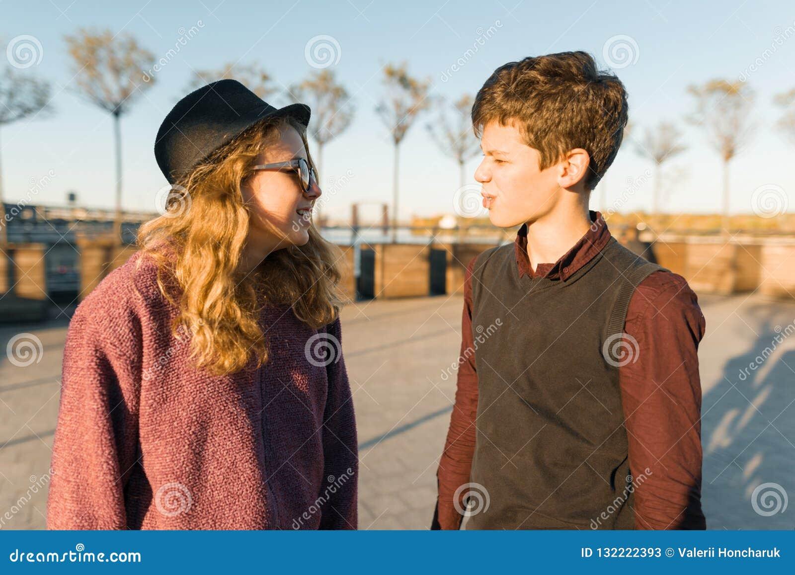 Porträt im Freien von ein paar Junge und Mädchen, die einander, lächelnde Jugendliche im Sonnenunterganglicht, goldene Stunde bet