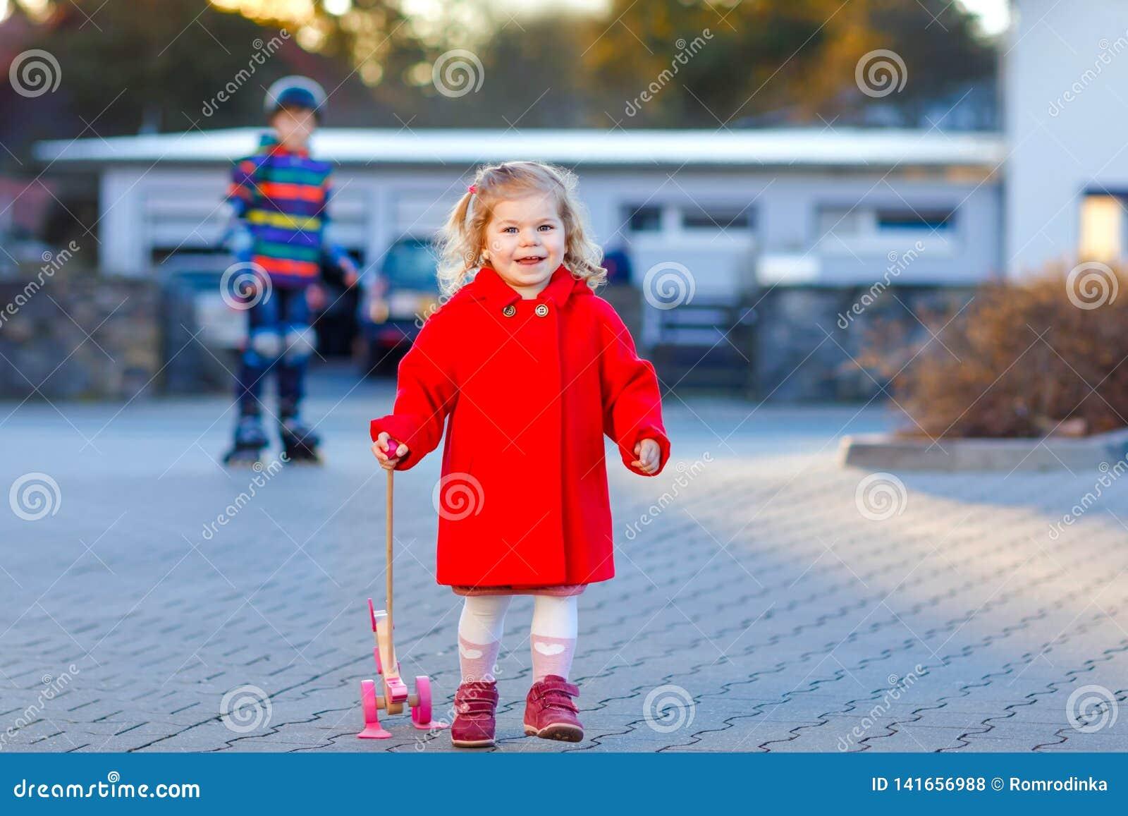 Porträt im Freien wenigen netten Kleinkindmädchens am sonnigen Tag roten Mantel-AON-Frühlinges mit hölzernem Spielzeug des Stoßes