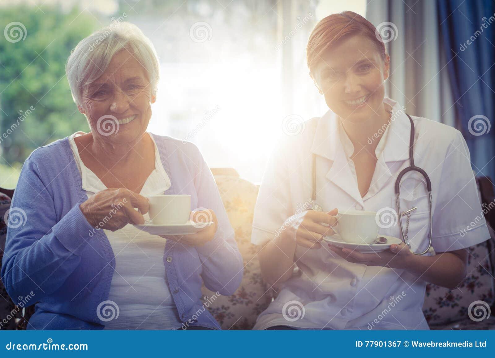 Porträt lächelnden Doktors und des Patienten, die Tee trinken
