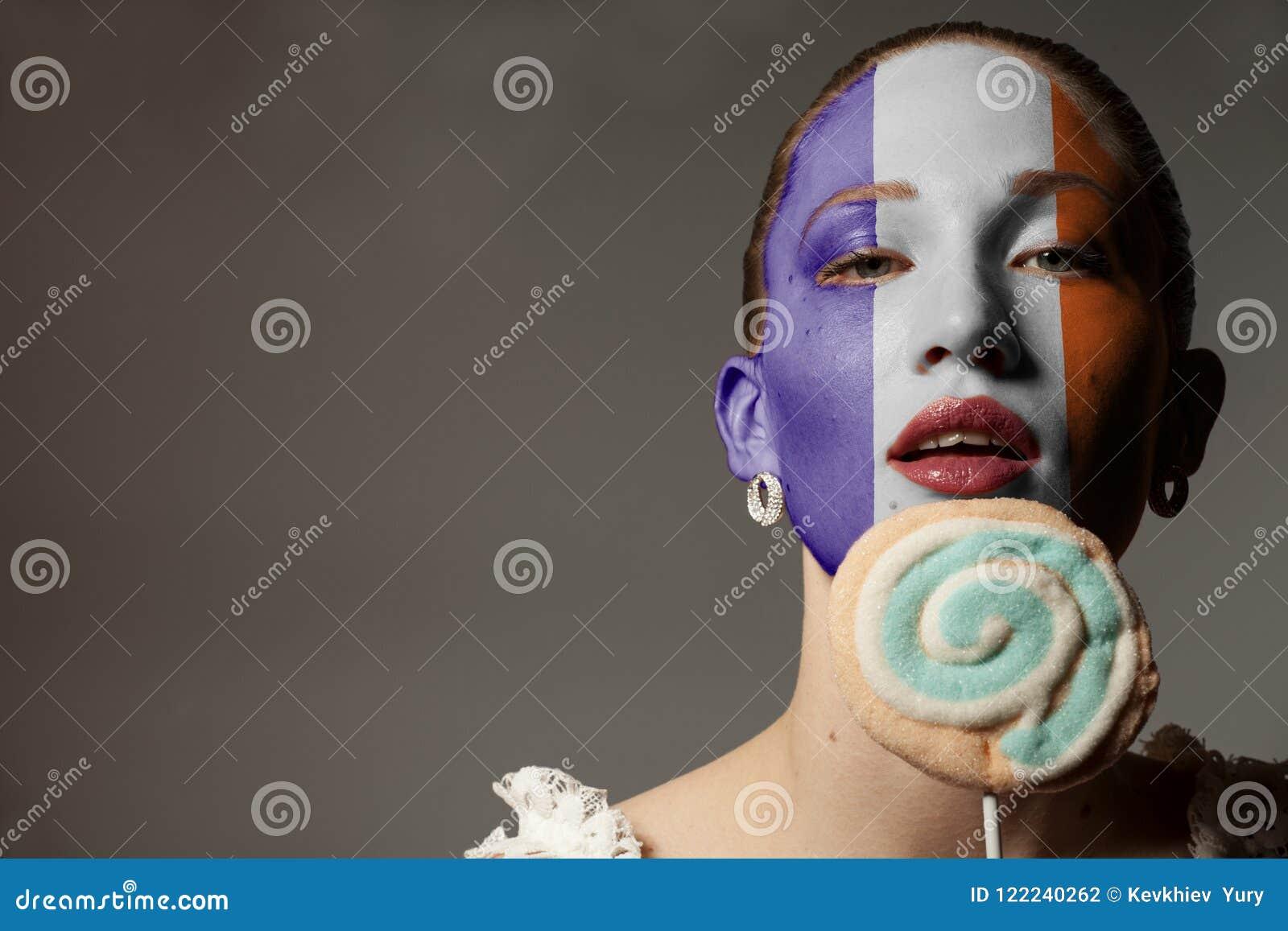 Porträt-Schönheits-Frau mit gemalter Frankreich-Flagge, die bunten Lutscher hält