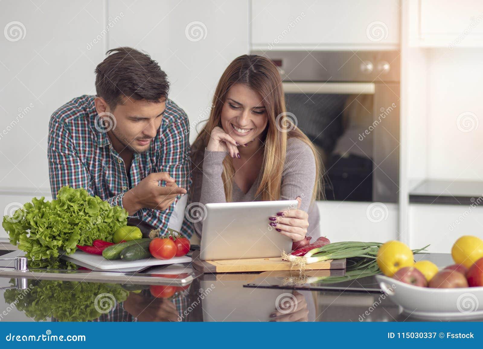 Porträt von den glücklichen jungen Paaren, die zusammen zu Hause in der Küche kochen