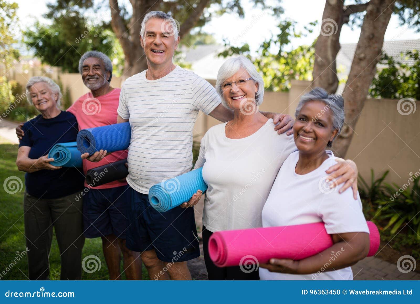 Porträt von den glücklichen multiethnischen Freunden, die Übungsmatten tragen