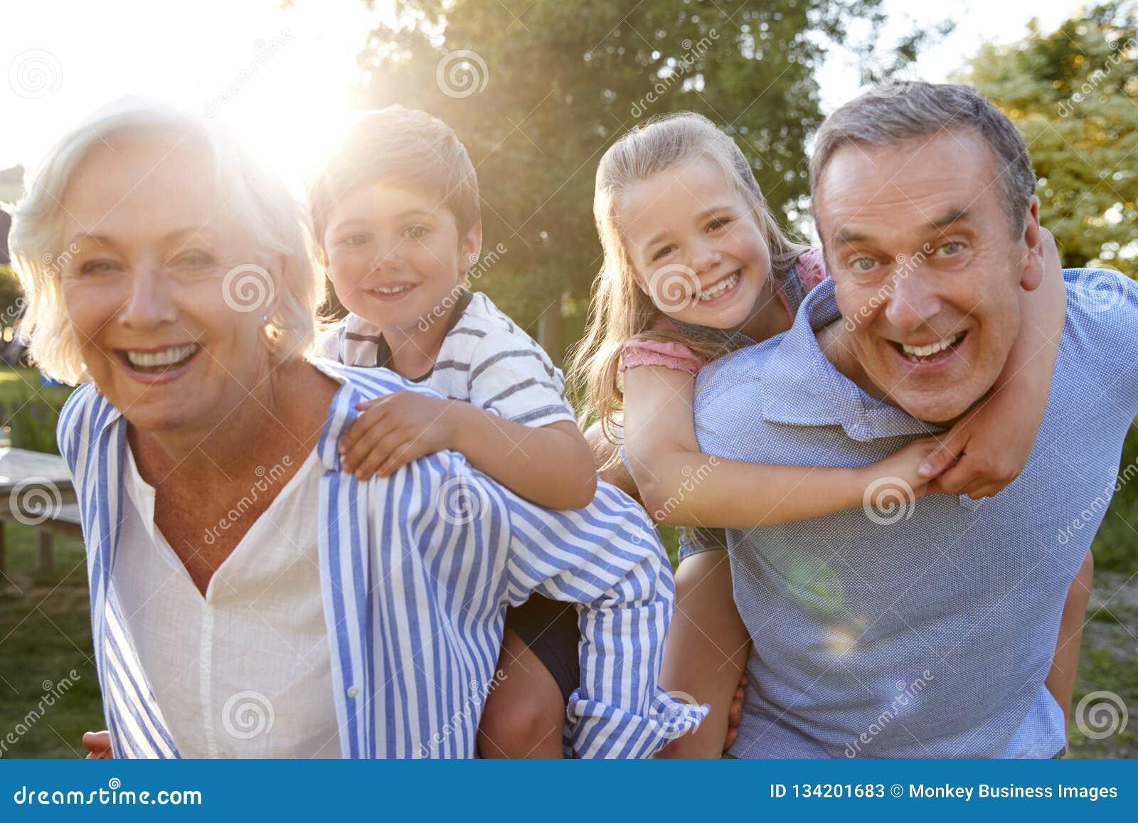 Porträt von den lächelnden Großeltern, die Enkelkinder geben, tragen Fahrfreien im Sommer-Park huckepack