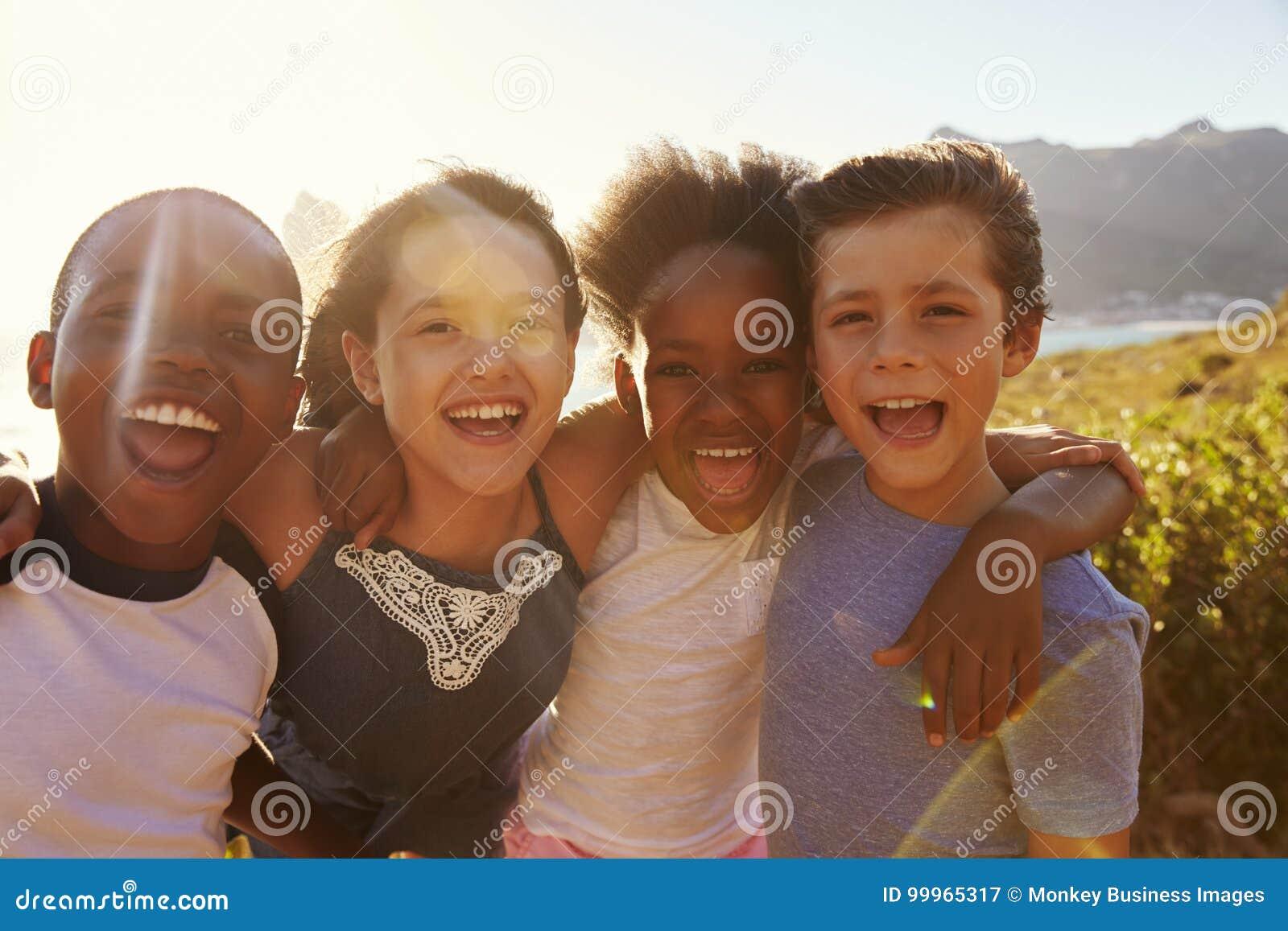 Porträt von den lächelnden Kindern, die auf Klippen durch Meer stehen