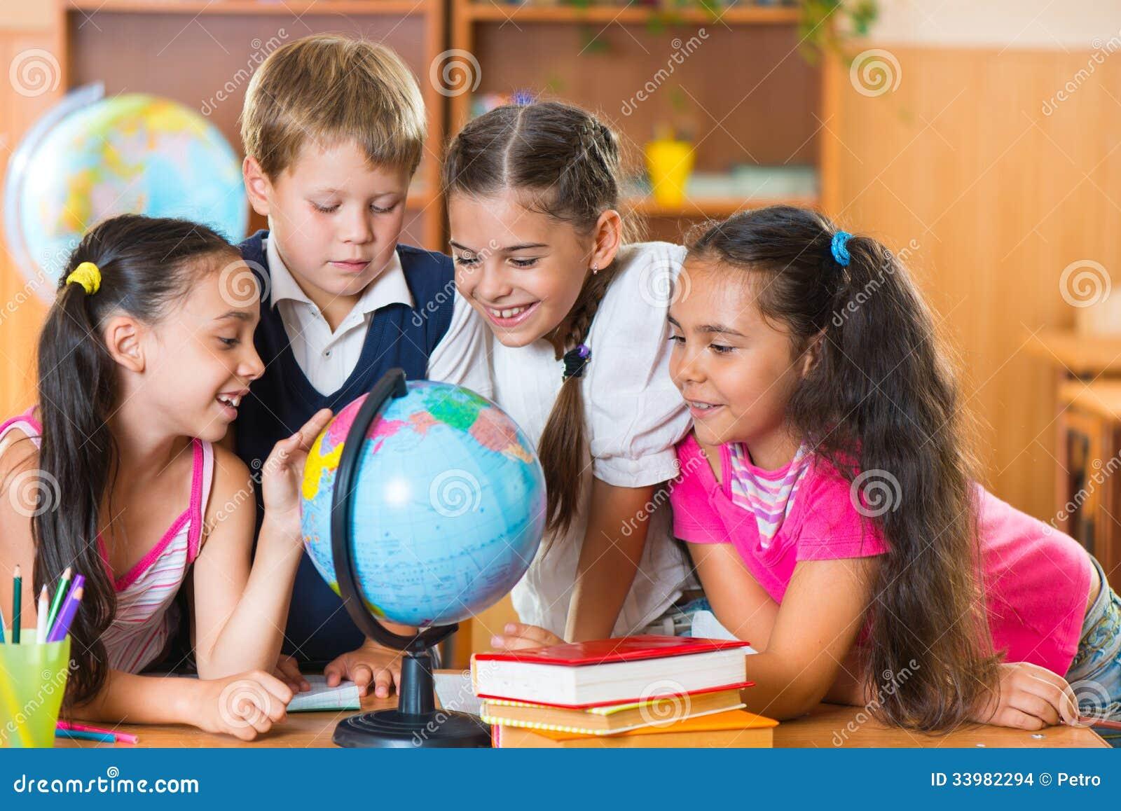 Porträt von den netten Schulkindern, die Kugel betrachten