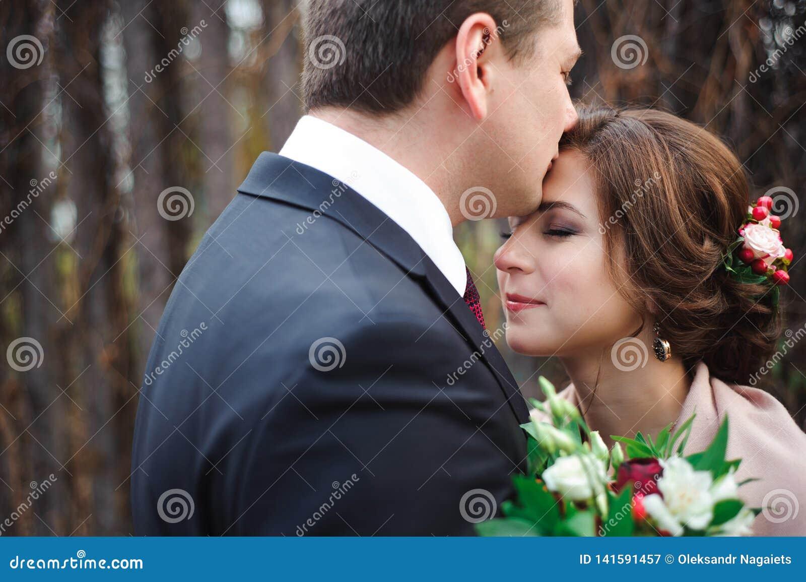 Porträt von glücklichen Jungvermählten in der Herbstnatur Glückliche Braut und die Umfassung und das Küssen pflegen