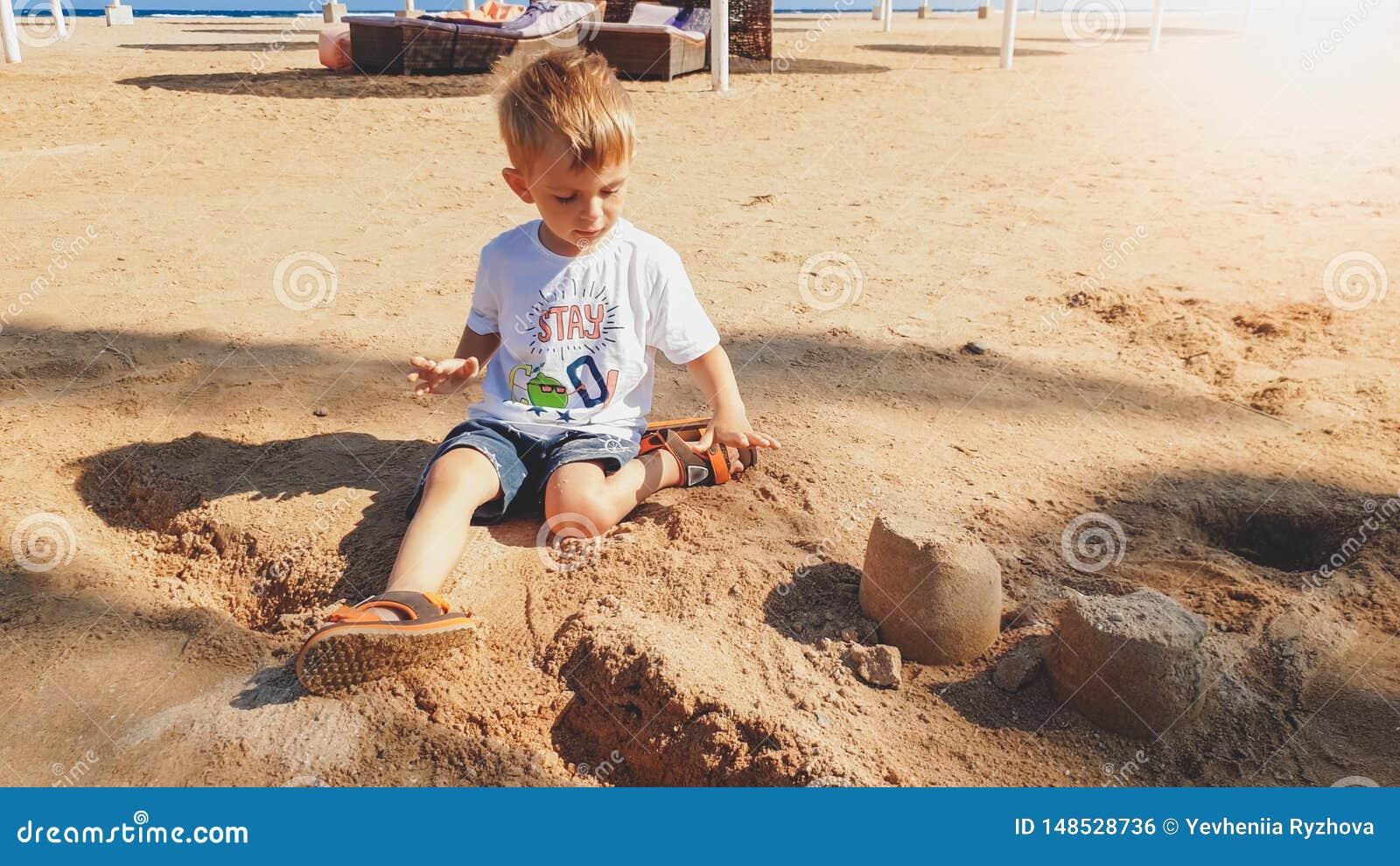 Porträt von netten 3 Jahren alten Kleinkindjungen, die auf dem sandigen Strand sitzen und mit Spielwaren und errichtendem Sandbur
