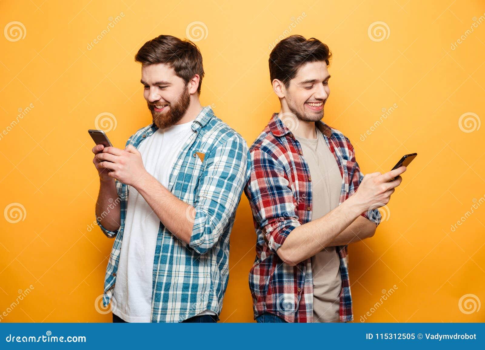 Porträt von zwei glückliche junge Männer, die Handys verwenden