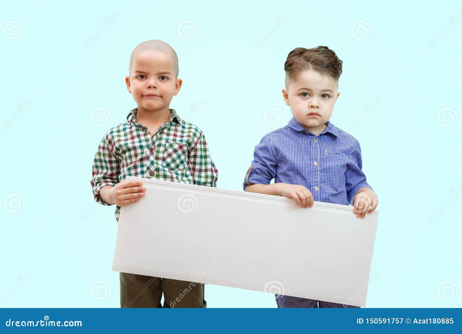 Porträt von zwei Jungen, die weißes Zeichen auf lokalisiertem Hintergrund halten