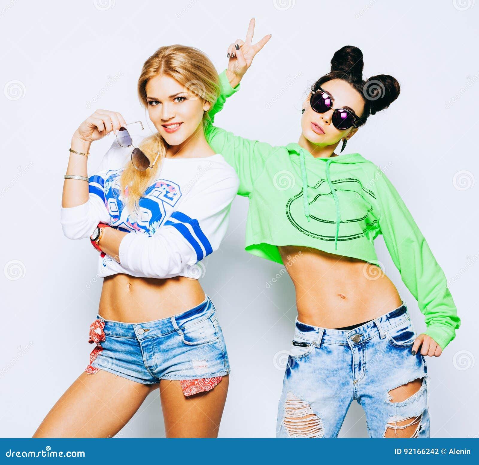 Porträt von zwei modischen kühlen Hippie-Mädchen im hellem Kalk und whigte Ausstattung, modische Frisuren und Make-up, Sonnenbril