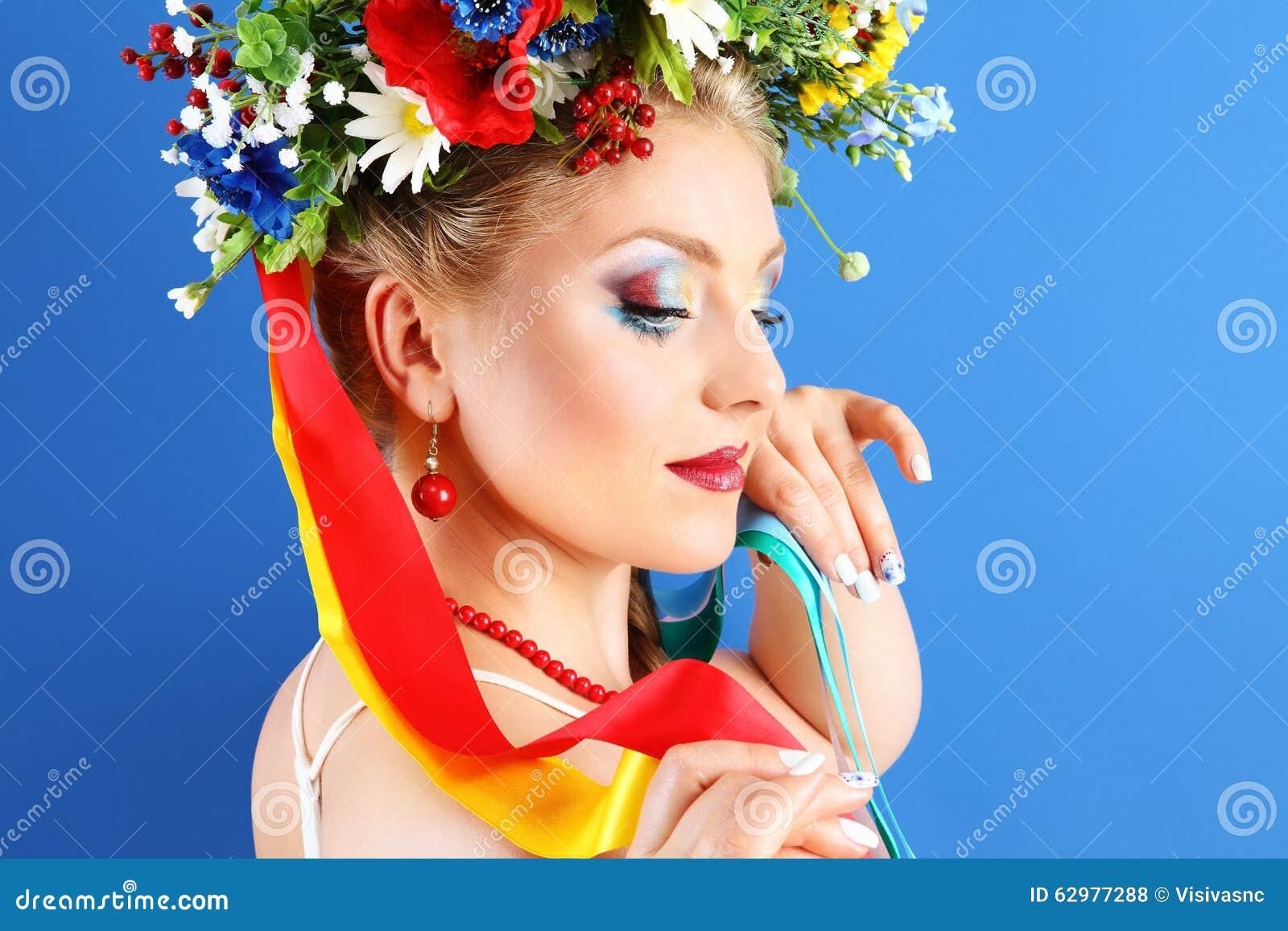 Porträtfrauenmake-up mit Blumen auf blauem Hintergrund