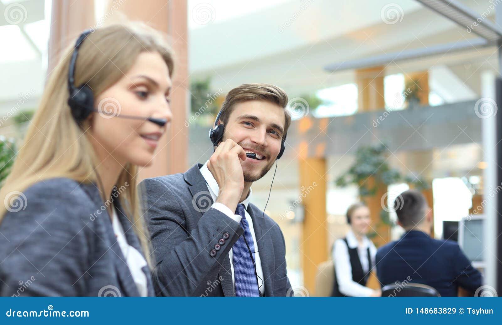 Portr?t der Call-Center-Arbeitskraft begleitet von seinem Team L?chelnder Kundenbetreuungsbetreiber bei der Arbeit