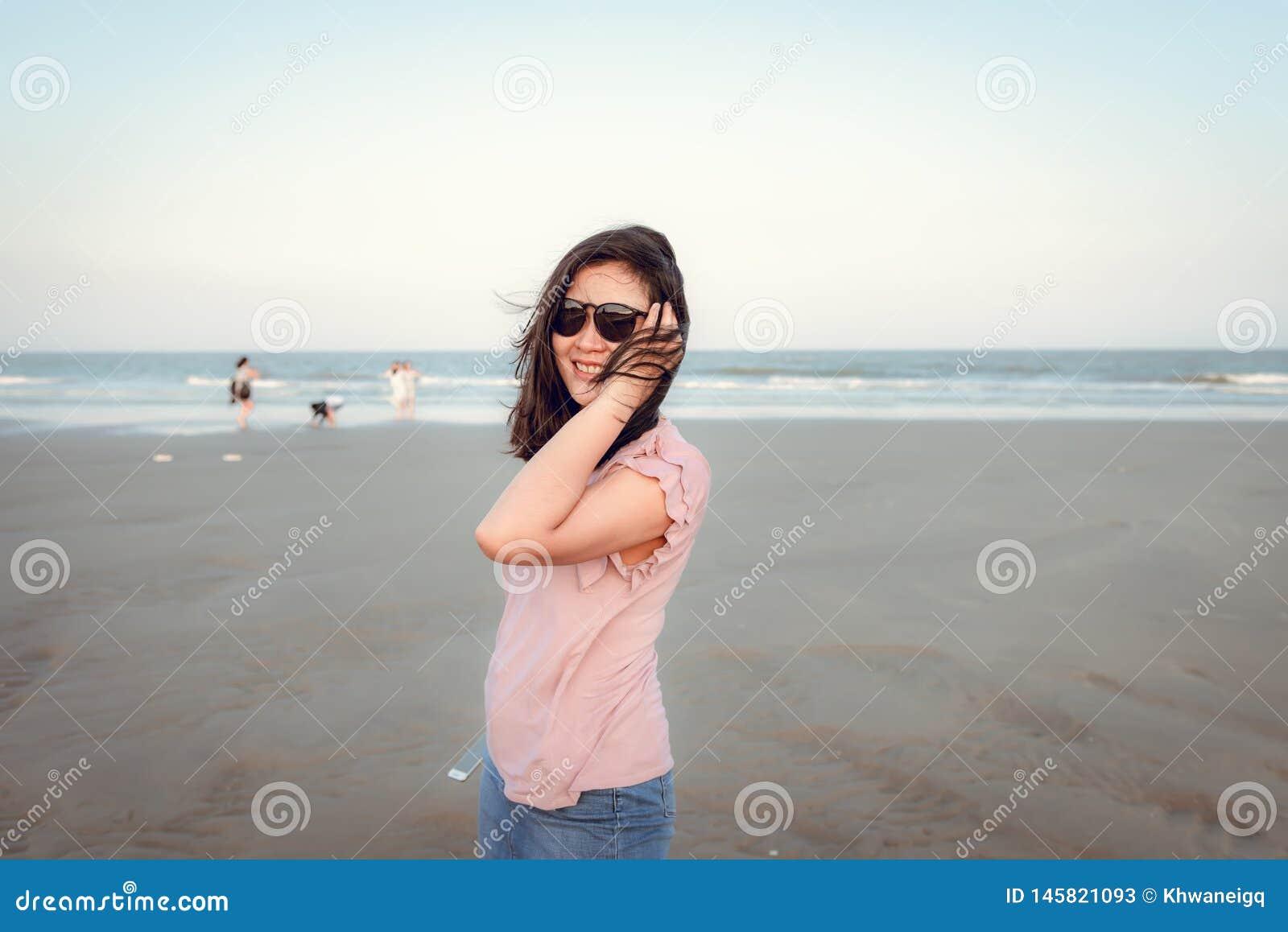 Portr?t der h?bschen Frau ist, entspannend genie?end und auf dem Strand in der Ferien-Zeit, asiatisches M?dchen-Gl?ck-Gef?hl im R