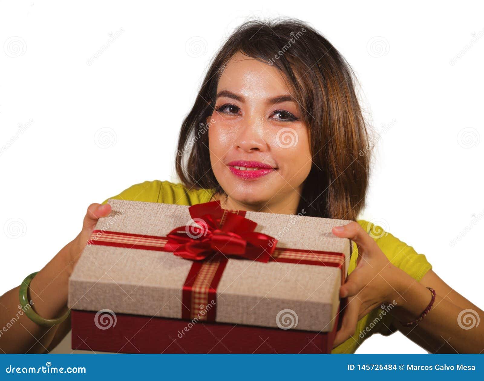 Portr?t der jungen gl?cklichen und sch?nen asiatischen indonesischen Frau, die Weihnachtsgeschenk- oder Geburtstagsgeschenkbox mi