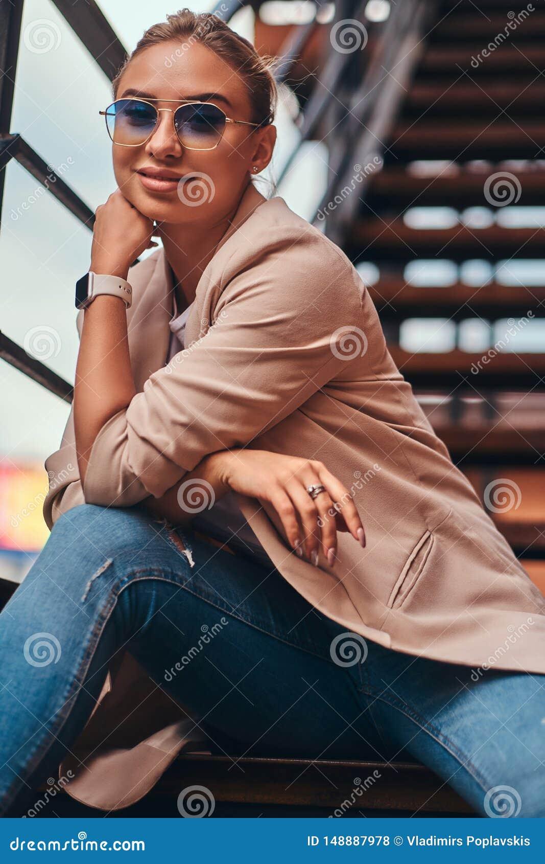 Portr?t der sch?nen zuf?lligen attraktiven Frau auf Stahltreppe am Hinterhof
