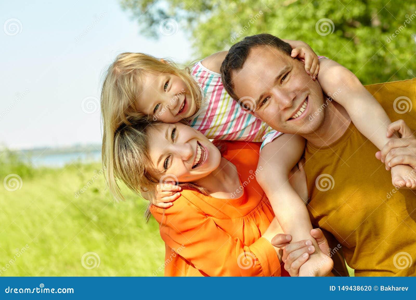 Portr?t einer gl?cklichen spielenden Familie drau?en Eltern mit Tochter im Sommer Mutter, Vati und Kind