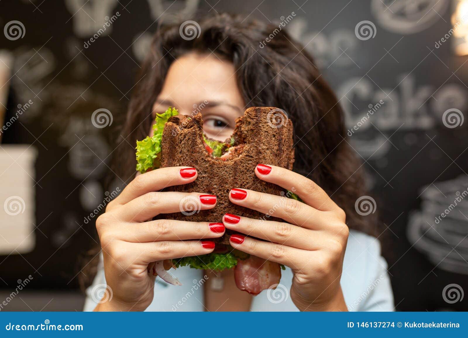 Portrai der jungen kaukasischen brunette Frau, die durch gebissenes Sandwich schaut