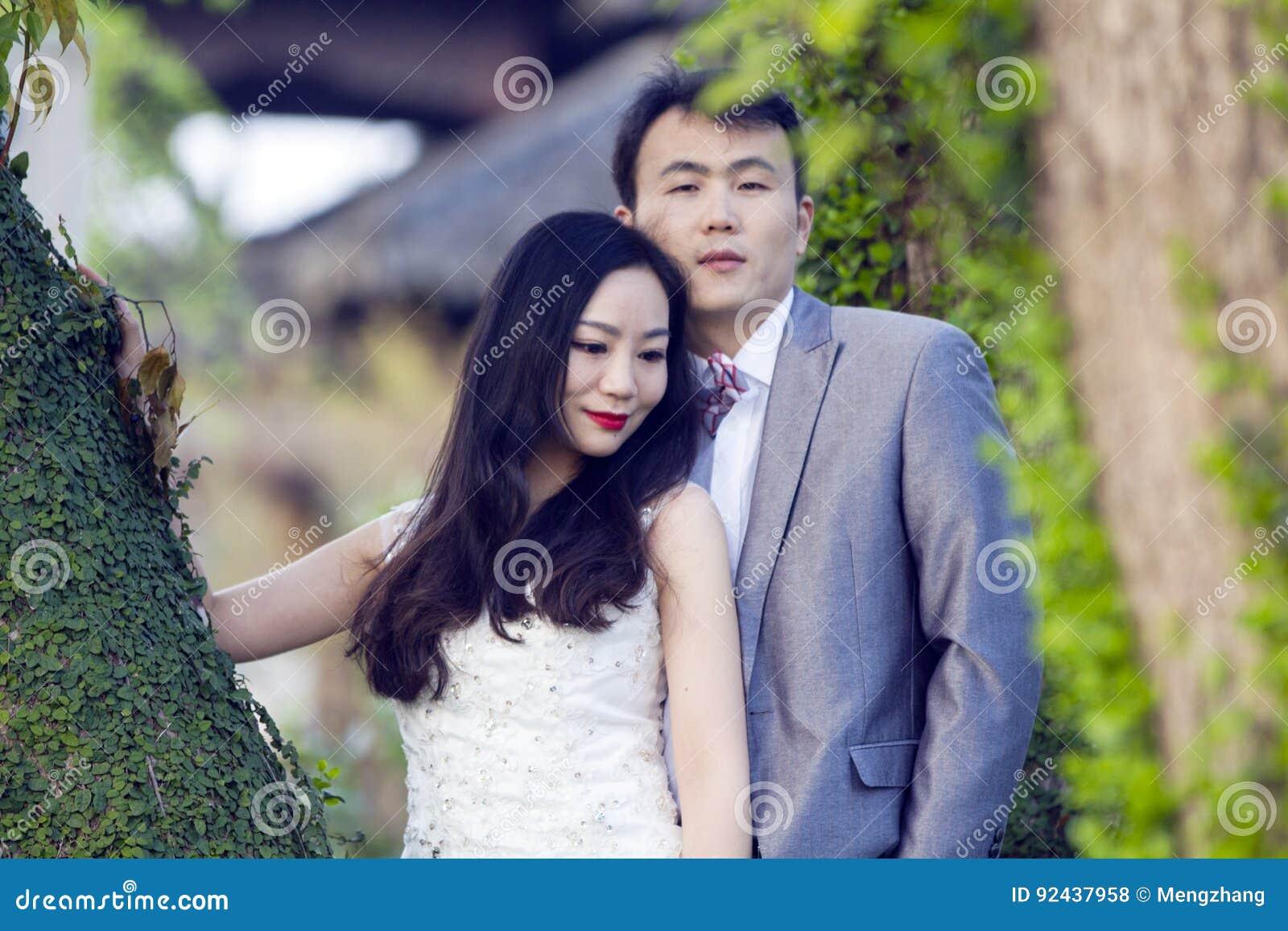 Portraint chino de la boda de los pares delante de árboles viejos y del edificio viejo
