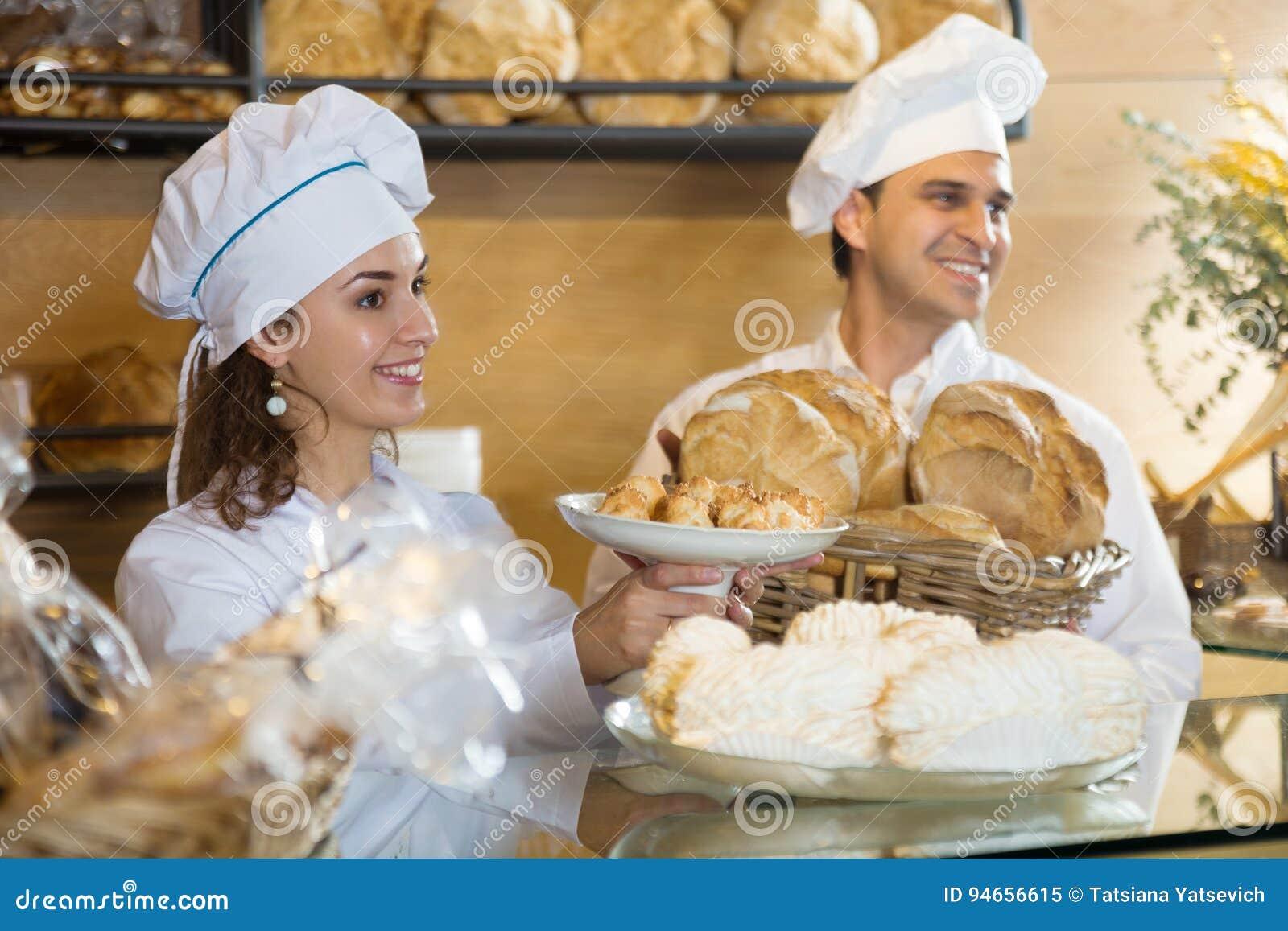 Portrair de los pasteles sonrientes del cocinero dos en panadería italiana