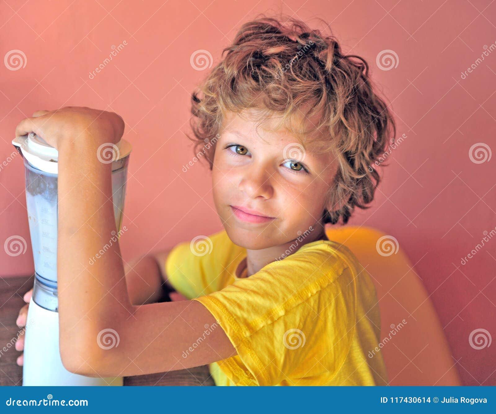 Portrair di un ragazzo felice che produce frappè per se stesso che si siede a