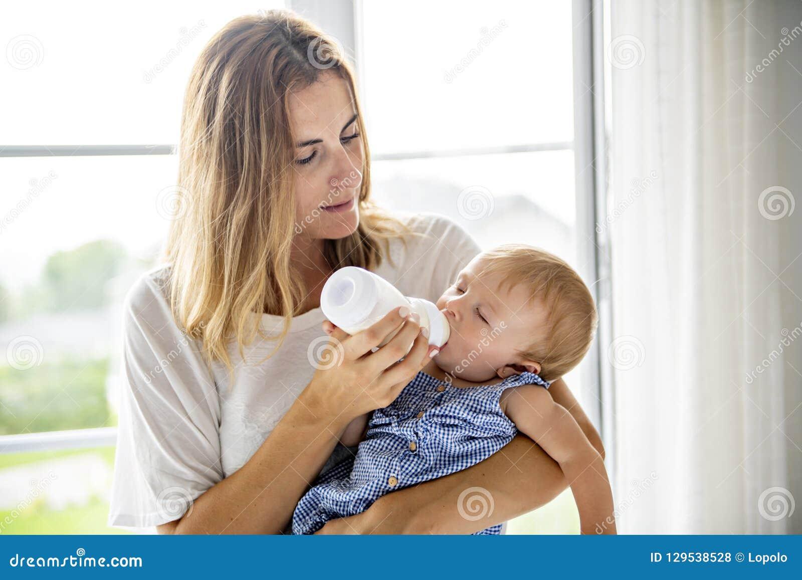 Portrait à la maison d un bébé avec la mère alimentant son enfant de bouteille