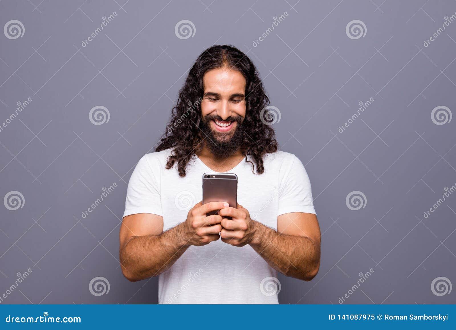 Portrait à lui il gentil type aux cheveux ondulés gai gai attirant employant le temps libre de nouvelle de dispositif d instrumen