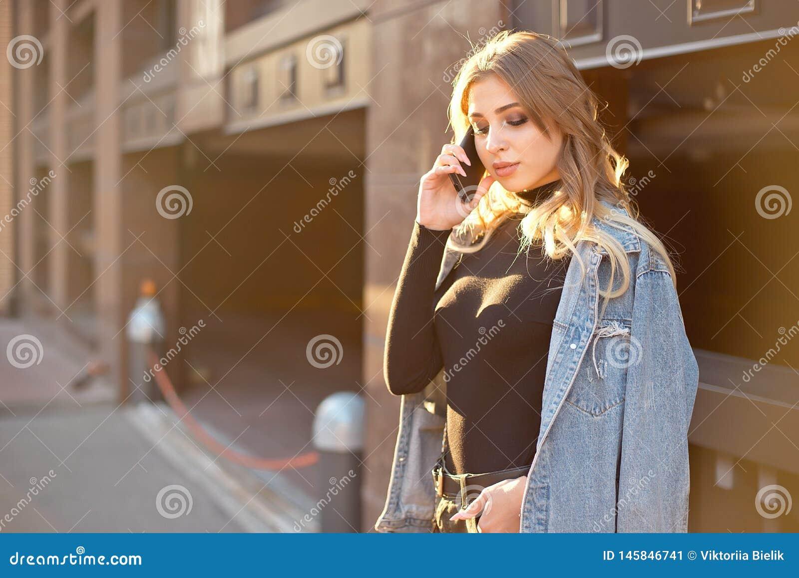 Portrait élégant émotif d une jeune femme blonde sur un plan rapproché de fond de paysage urbain dans le coucher de soleil