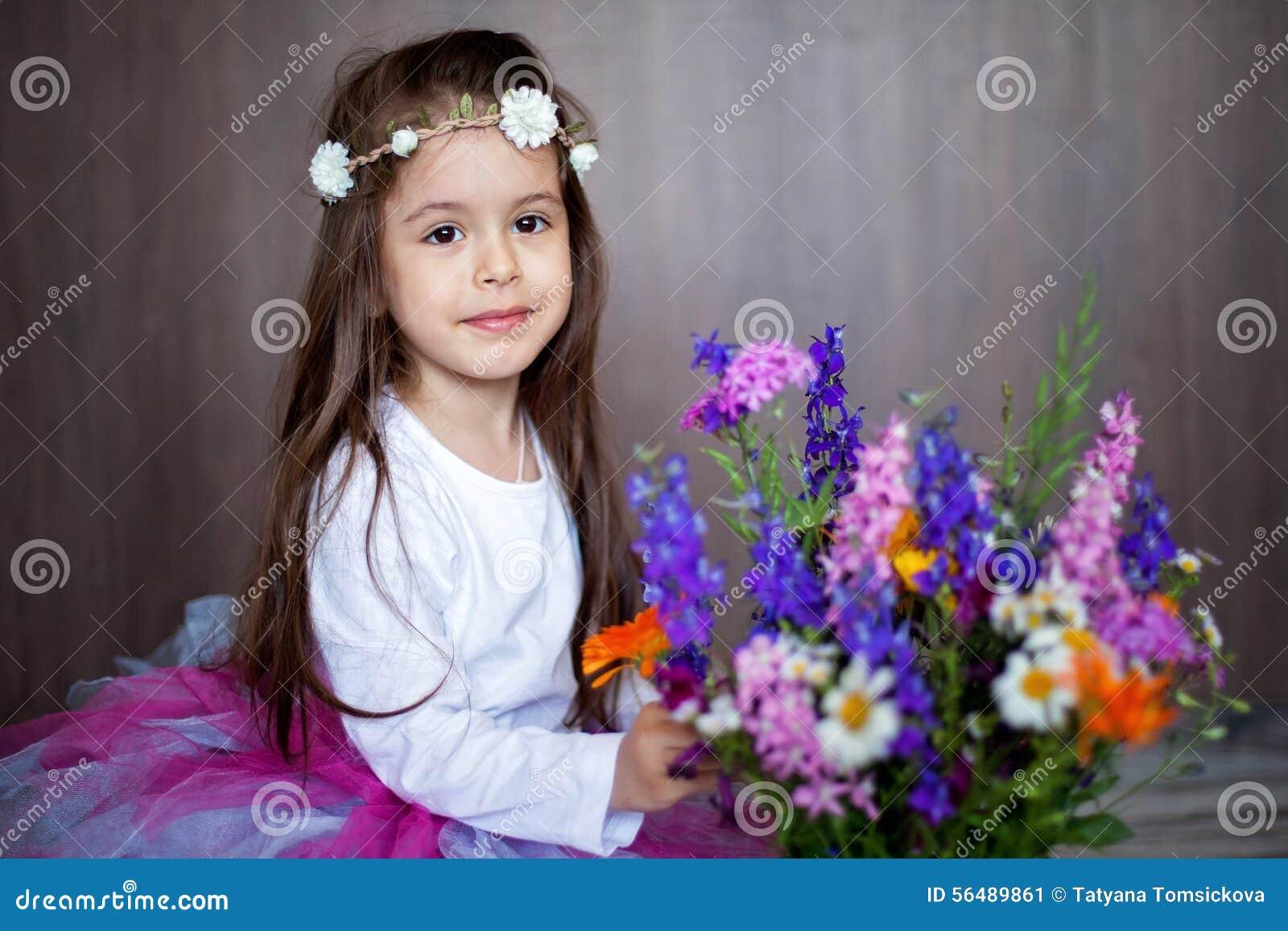 Portrait étroit d une petite fille de sourire douce tenant le bouquet de