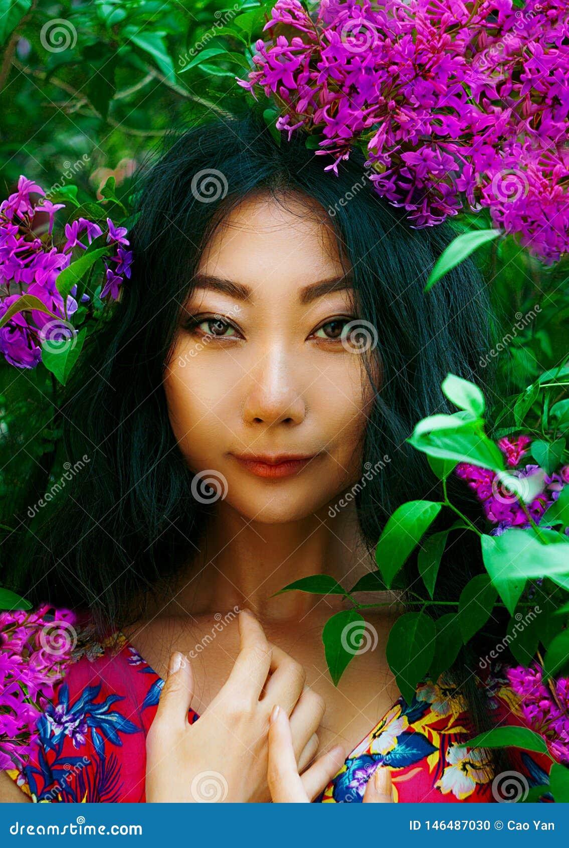 Portrait étroit de femme asiatique avec la fleur rose dehors