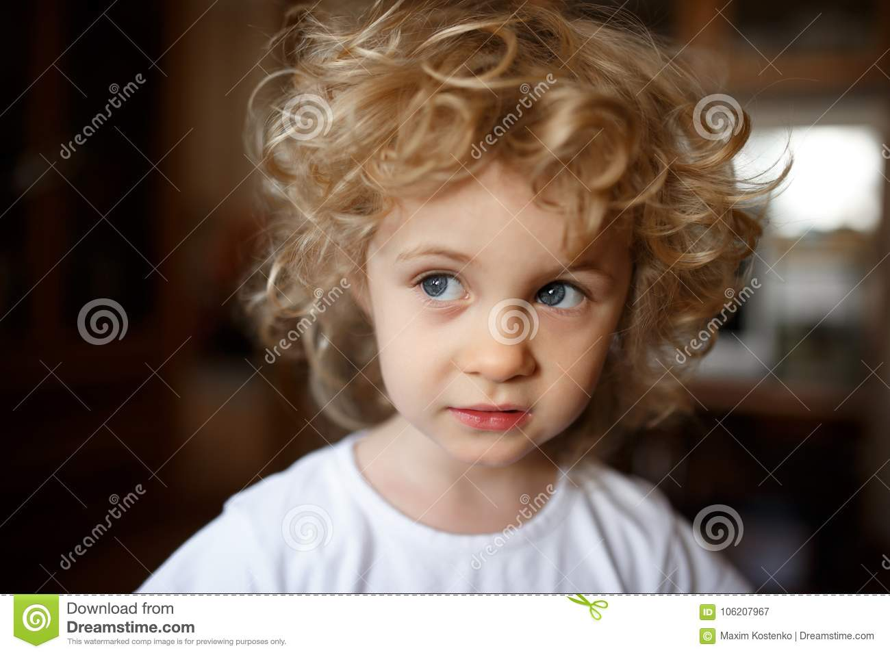 Portrait of adorable little blonde girl with curly hair.