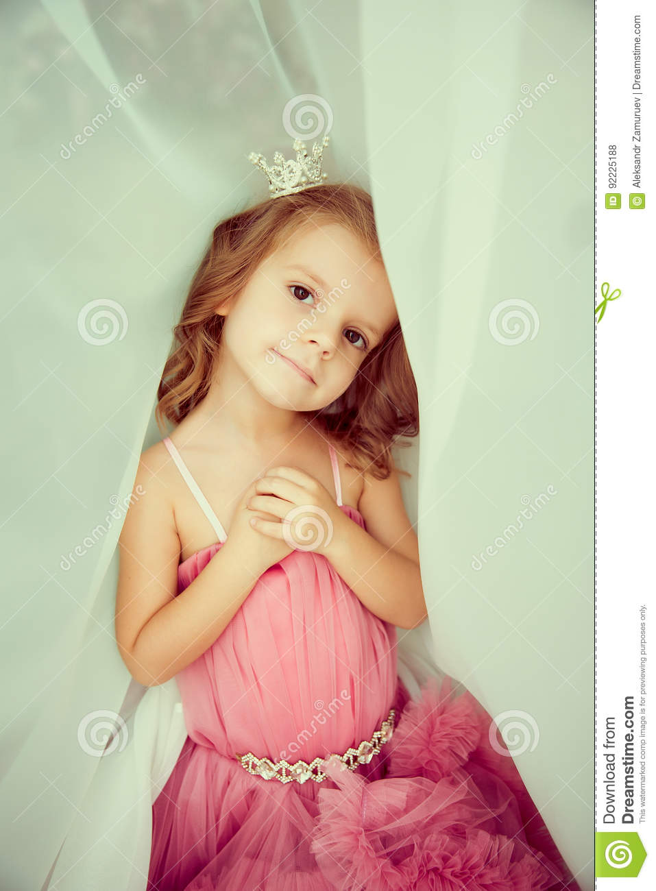Portrait of adorable little girl in pink dress and tiara