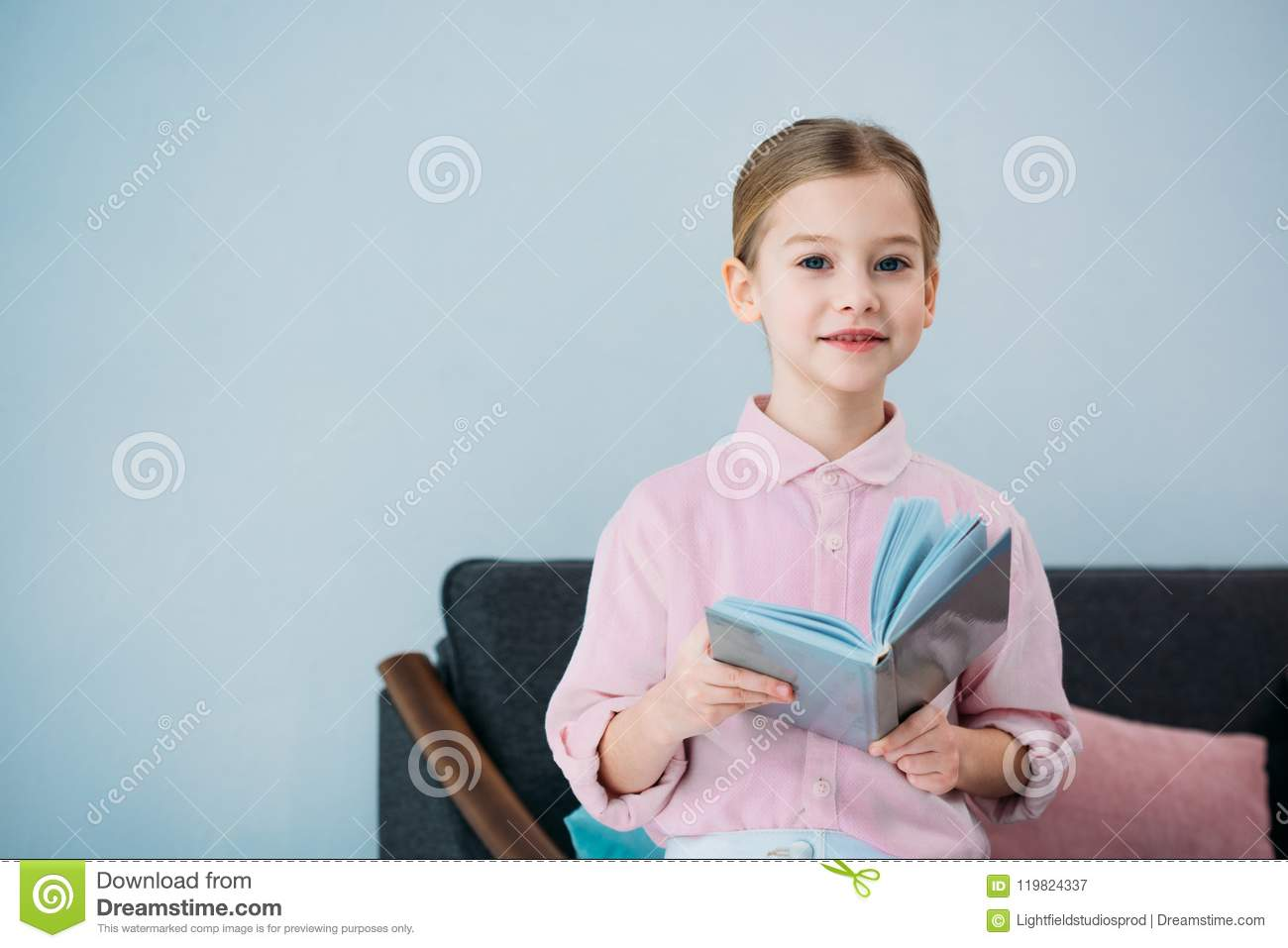 portrait of adorable little kid with book sitting on sofa