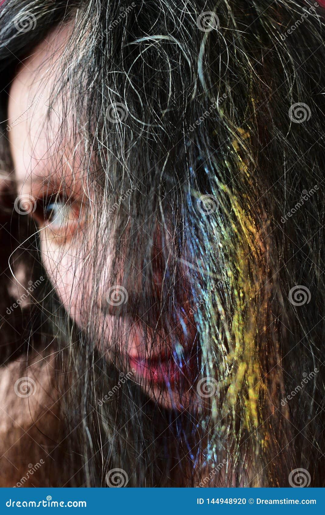 Portrait af une jeune femme avec un arc-en-ciel sur les cheveux foncés
