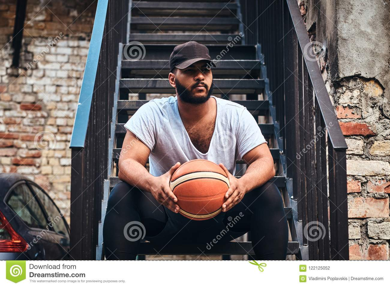 Portrait of an African-American bearded guy in cap dressed in a white t-shirt and sports shorts holds a basketball