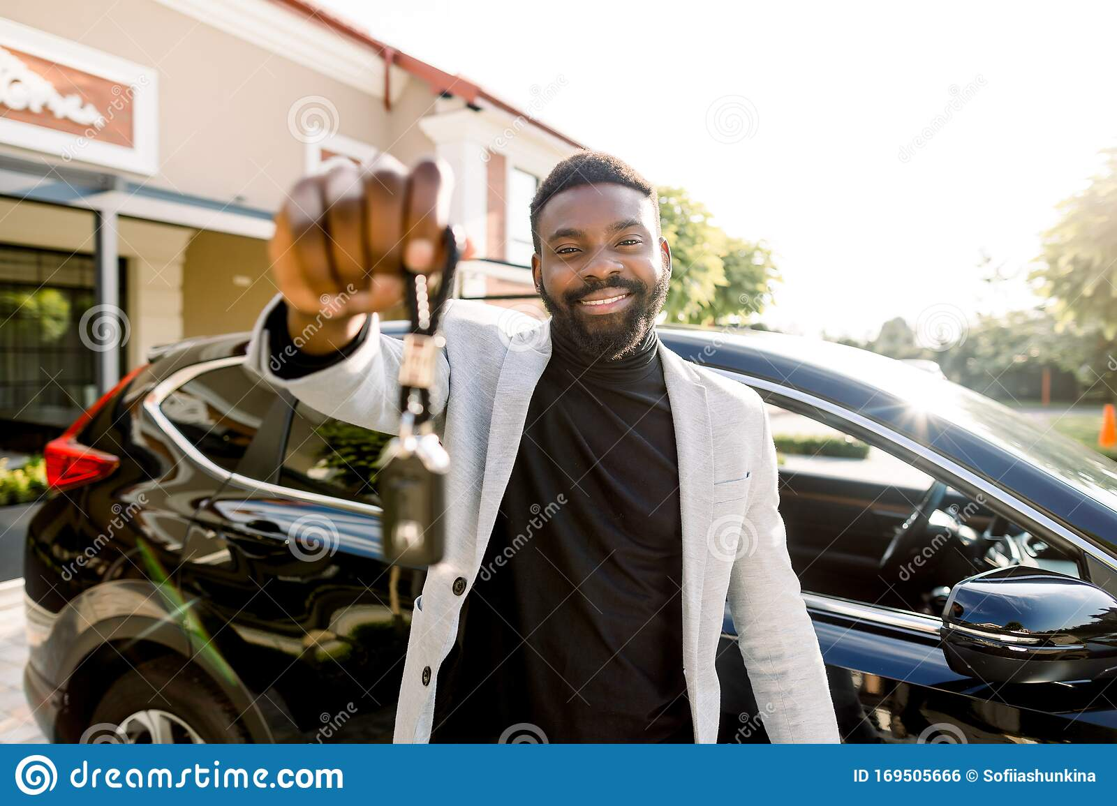 Portrait Of African Man Car Seller Holding Car Keys Attractive Cheerful Young African Man Smiling Showing Car Keys To Stock Photo Image Of Buying Owner 169505666