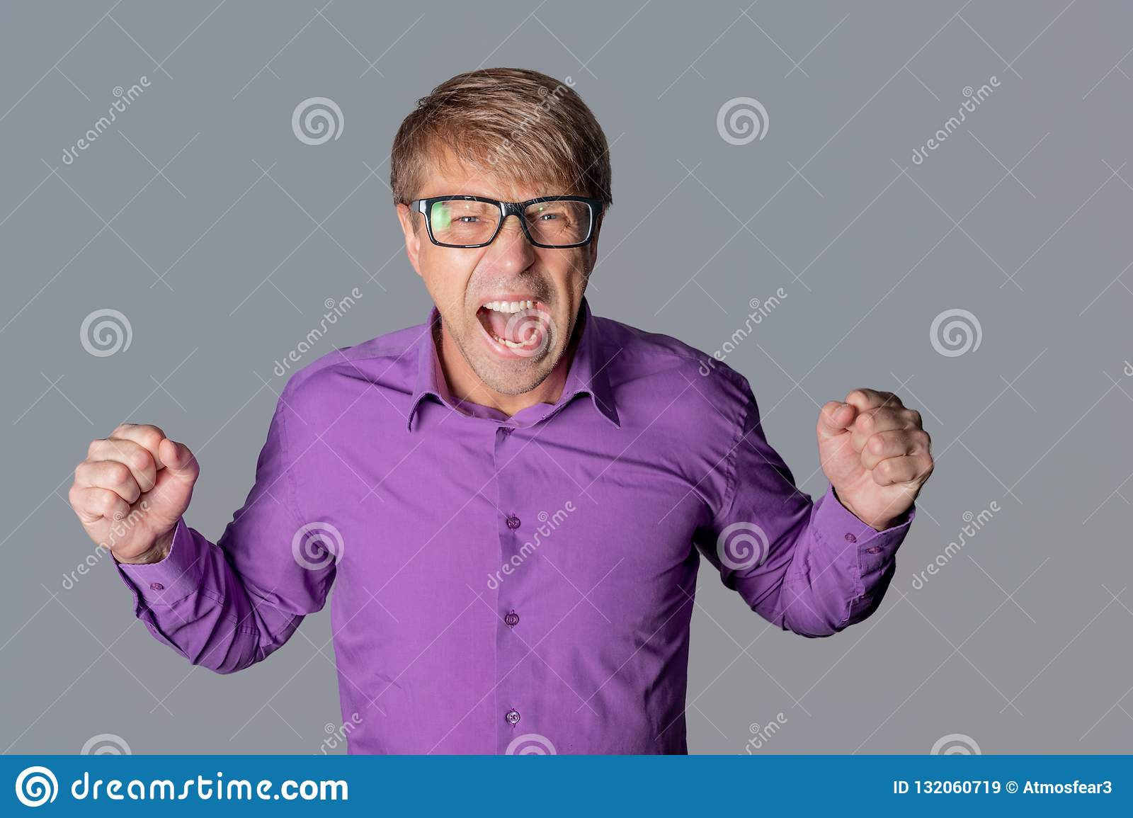 Portrait of a angry man with glasses staring at camera, shows finger and shouting over gray background