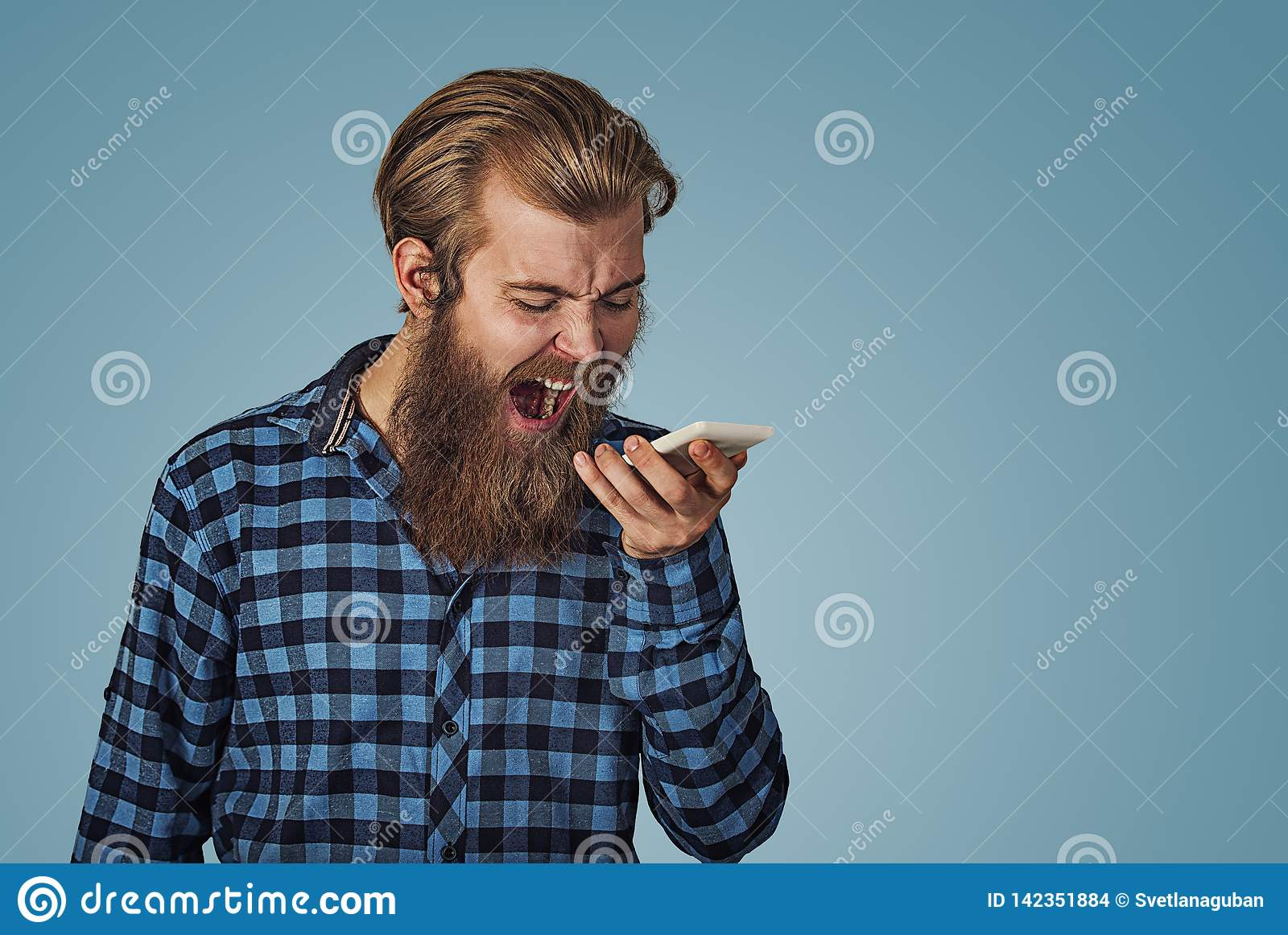 Angry young man screaming on mobile phone