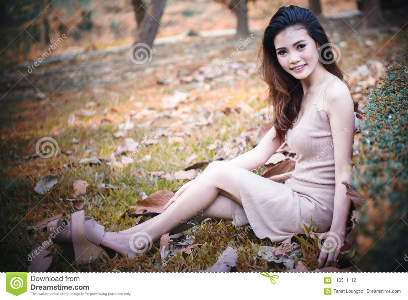 Asia beautiful Girl sitting in park on green grass