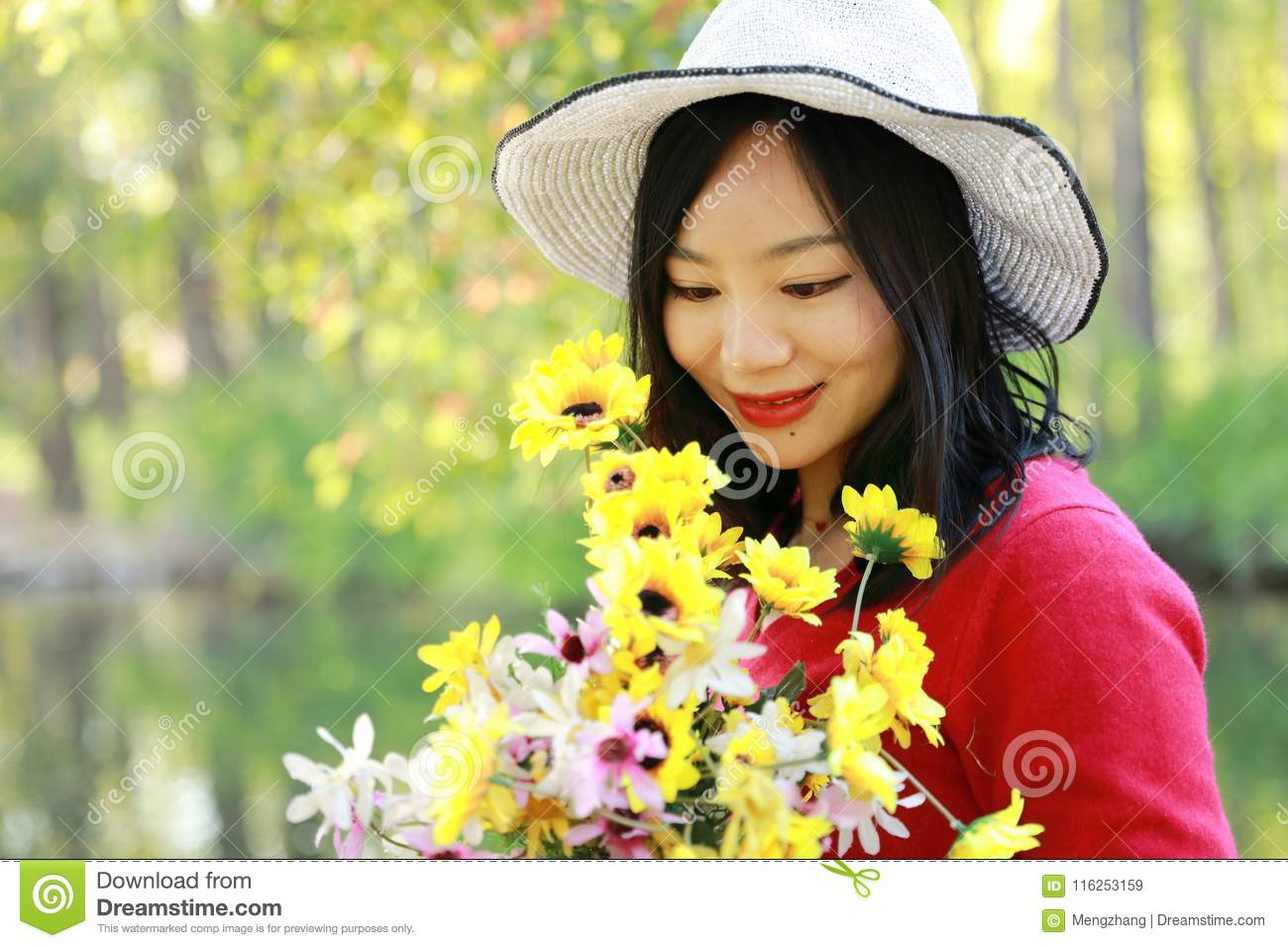 Happy Asian Chinese woman beauty girl smile hold a bunch of flower walk by lake in forest spring park sit on bench enjoy cozy life