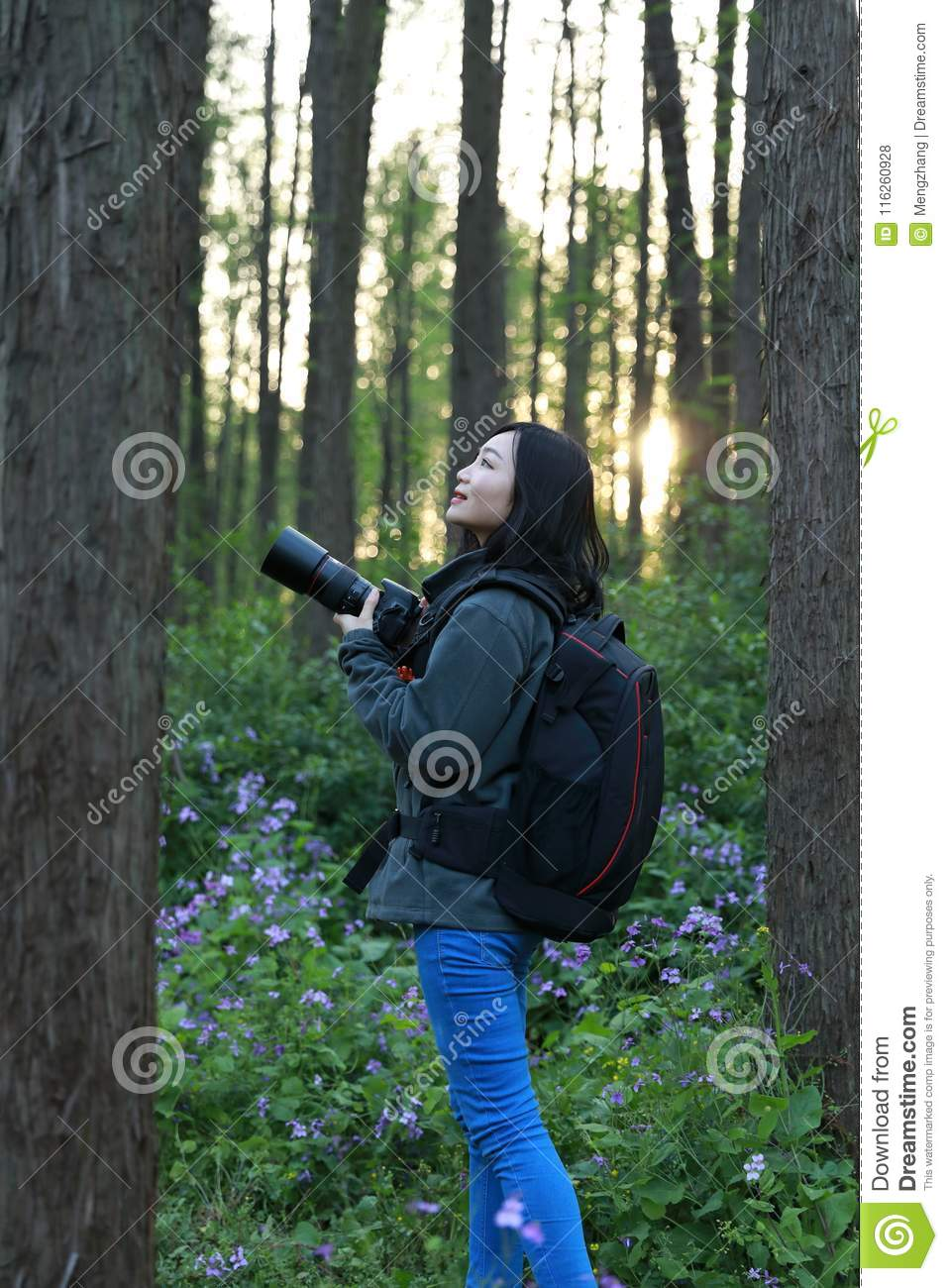 Portrait of a Asian Chinese nature woman photographer look at her camera screen in a spring park forest surround by flowers
