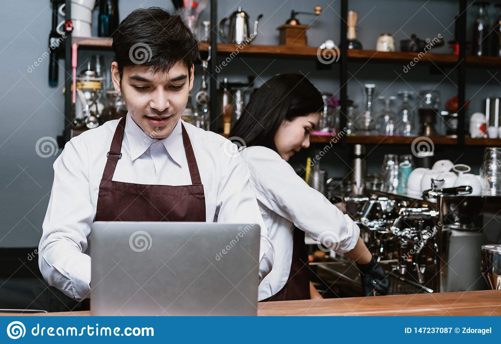 Portrait of Asian couple small business owner using laptop at counter bar in cafe, Service mind and Startup Owner small business