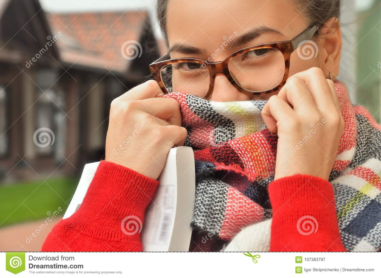 Portrait of an Asian girl in glasses, she screwed her face with a scarf,  only her eyes and hands are visible. The hair is tied to the knot.