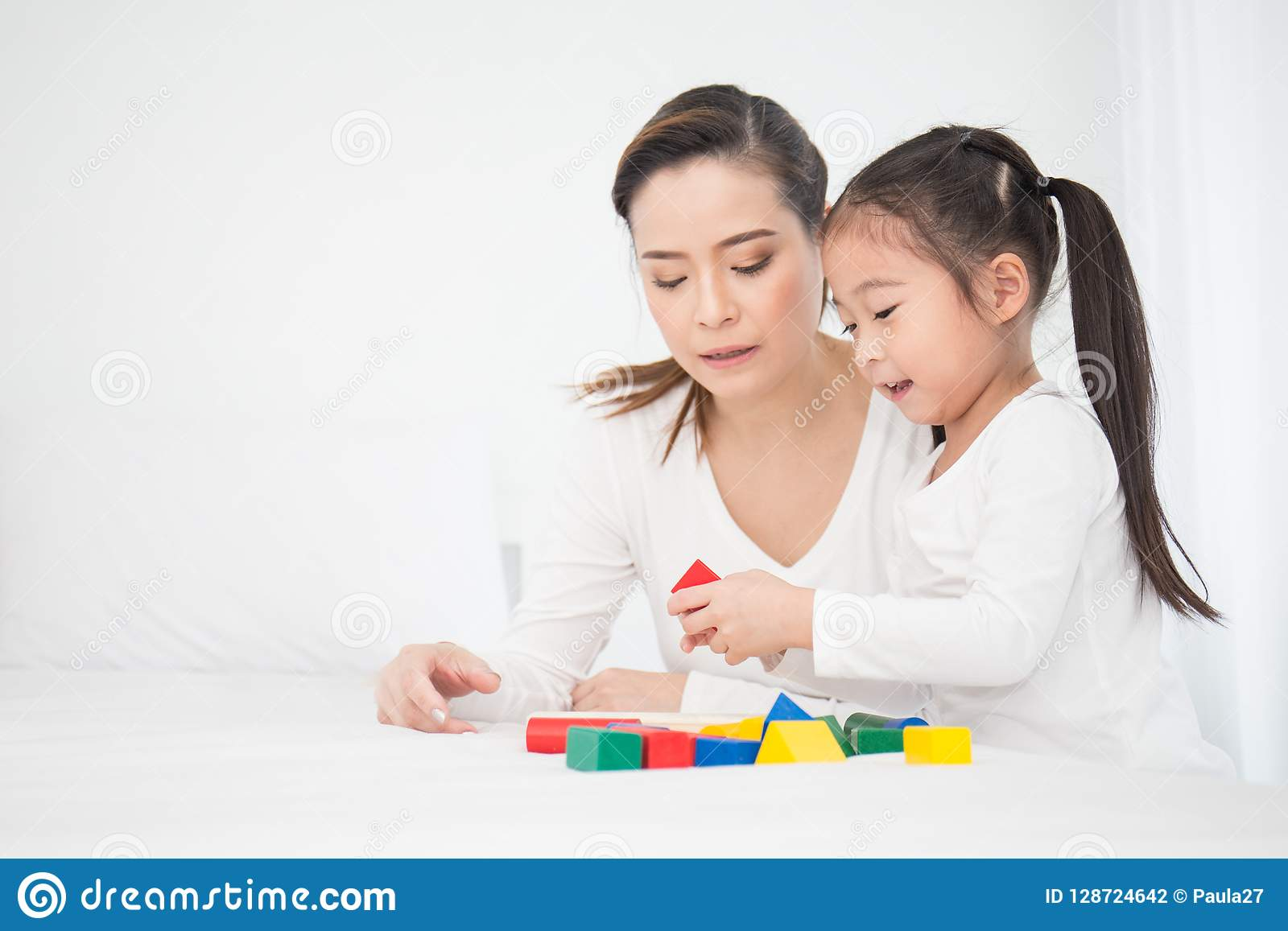 Portrait of asian little cute girl playing colorful blocks with her mother over white background.